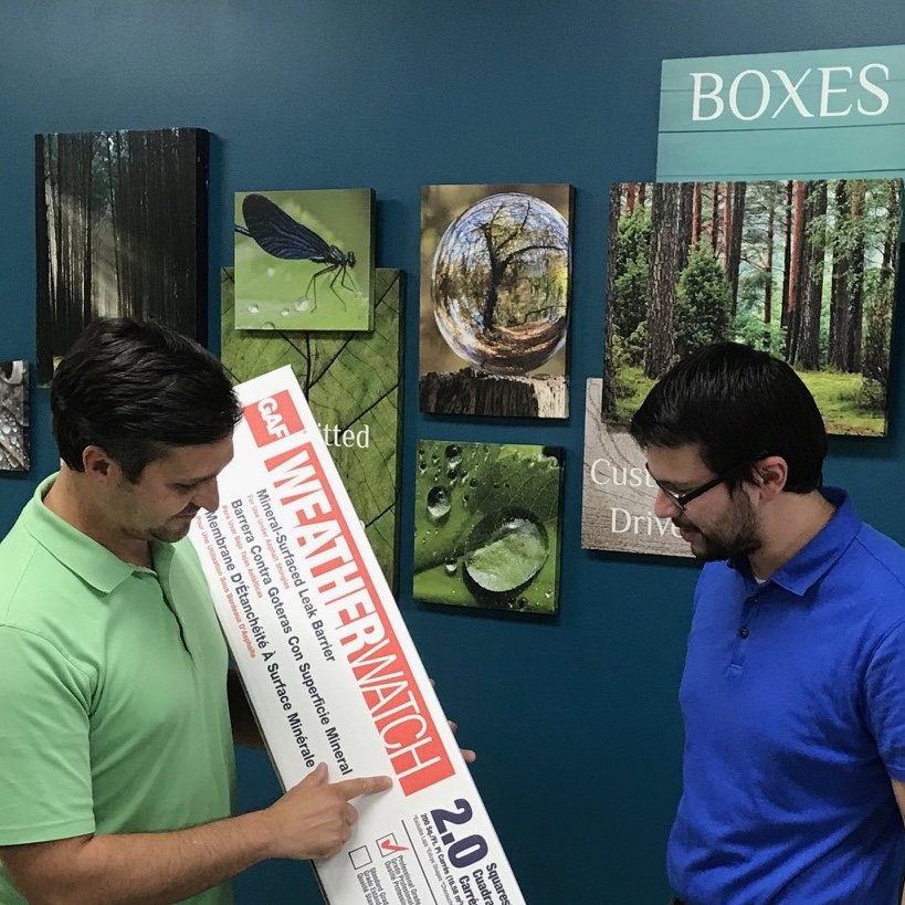 One main in a green shirt holding a box and a second man in a blue shirt looking at the box.